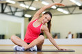 Smiling woman stretching on mat in the gym fitness sport training and lifestyle concept Stock Image