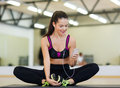 Smiling woman stretching on mat in the gym fitness sport training technology and lifestyle concept with smartphone Stock Image