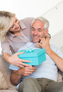 Smiling woman surprising mature man with a gift on sofa portrait of women men at home Stock Photography