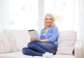 Smiling woman with tablet pc computer at home technology and internet concept sitting on the couch Stock Photography