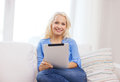 Smiling woman with tablet pc computer at home technology and internet concept sitting on couch Royalty Free Stock Image