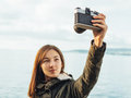 Smiling woman takes photographs selfie portrait young brunette with old photo camera on coastline on background of sea Royalty Free Stock Photos