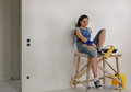Smiling woman taking a break from painting young the wall relaxing on wooden trestle with roller in her hand Stock Images