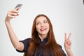 Smiling woman taking selfie with mobile phone showing victory sign Royalty Free Stock Photo