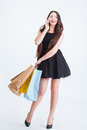Smiling woman talking on mobile phone and holding shopping bags Royalty Free Stock Photo