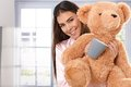 Smiling woman with teddy bear and coffee mug happy cuddling in morning at camera Royalty Free Stock Photography