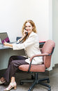 Smiling woman on telephone at office desk businesswoman phone talking and taking notes in workstation Stock Photo