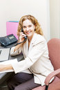 Smiling woman on telephone at office desk businesswoman phone in workstation Royalty Free Stock Photo