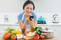 Smiling woman text messaging in front of vegetables in kitchen young the at home Stock Images