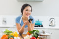 Smiling woman text messaging in front of vegetables in kitchen young the at home Royalty Free Stock Photos