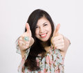 Smiling woman with thumbs up gesture Stock Photo