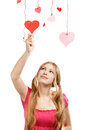 Smiling woman touchs designer red and pink paper valentine heart beautiful young hearts hanging on colored threads isolated on Stock Image