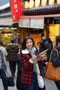 Smiling woman tourist hold map on street in japan Royalty Free Stock Photos