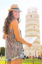 Smiling woman tourist holding map at Leaning Tower of Pisa Royalty Free Stock Photo