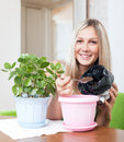 Smiling woman transplants kalanchoe plant flowerpot her home Stock Images