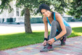 Smiling woman tying her shoelace outdoors sporty and looking at camera Stock Photos