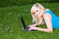 Smiling woman using her laptop on the grass Royalty Free Stock Photos