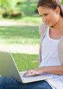 Smiling woman using her laptop while sitting on the lawn Stock Photo