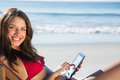 Smiling woman using her tablet while relaxing on her deck chair the beach Royalty Free Stock Photo