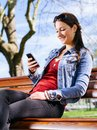 Smiling woman using smartphone on park bench photo of a beautiful young a while sitting in a a Royalty Free Stock Photo