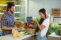 Smiling woman with vendor at the counter at grocery store Royalty Free Stock Photo