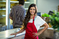 Smiling woman vendor standing at the counter in grocery store Royalty Free Stock Photo