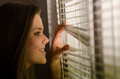Smiling woman waiting for someone profile of the beautiful girl looking through venetian blinds Stock Photography