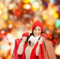 Smiling woman in warm clothers with shopping bags retail and sale concept happy winter clothes Stock Images