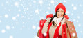 Smiling woman in warm clothers with shopping bags retail and sale concept happy winter clothes Stock Image