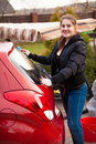 Smiling woman washing red car at backyard portrait of Stock Photo