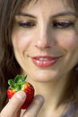 Smiling woman  watching strawberry fruit Royalty Free Stock Photography