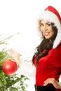 Smiling woman wearing santa claus decorating christmas tree Royalty Free Stock Photo