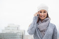 Smiling woman with winter clothes on having a call outdoors cold grey day Royalty Free Stock Photography