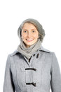 Smiling woman in a winter ensemble beautiful warm grey wth an overcoat cap and scarf isolated on white Stock Photo