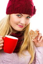 Smiling woman in woolen cap and shawl with gingerbread cookies and tea decorated or christmas red cup of hot christmas time white Stock Photo