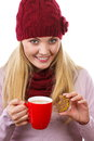 Smiling woman in woolen cap and shawl with gingerbread cookies and tea white background christmas time decorated or red cup of hot Royalty Free Stock Images