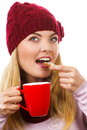 Smiling woman in woolen cap and shawl with gingerbread cookies and tea white background christmas time decorated or red cup of hot Stock Photography
