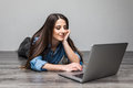 Smiling woman working on laptop on floor Royalty Free Stock Photo