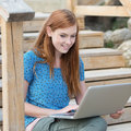 Smiling woman working on a laptop outdoors sitting flight of wooden stairs Royalty Free Stock Images