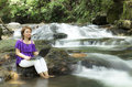 Smiling woman working on laptop at waterfall Royalty Free Stock Images