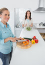 Smiling women cooking together and looking at camera in the kitchen Stock Photos