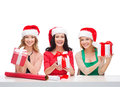 Smiling women in santa helper hats with gift boxes christmas x mas winter happiness concept three Stock Photo