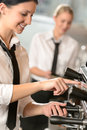 Smiling women waitress preparing coffee machine with Stock Image
