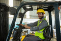 Smiling worker driving a forklift car in factory Royalty Free Stock Photo