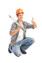 A smiling worker holding a construction bubble level and giving Royalty Free Stock Images