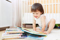 Smiling 2 years toddler reading books Royalty Free Stock Photo