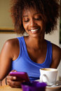 Smiling young african woman using cellphone at cafe close up portrait of a Stock Image