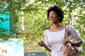 Smiling young african woman walking with mobile phone and purse Royalty Free Stock Photo