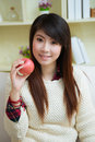 Smiling young asian woman with apple at home Stock Image