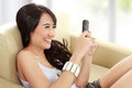 Smiling young beauty girl with handphone sitting on sofa and hold the Royalty Free Stock Photos